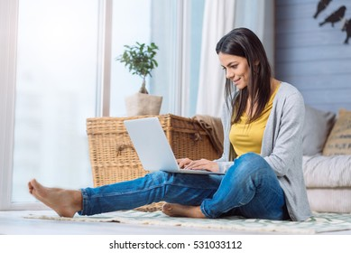 Positive woman using the laptop at home