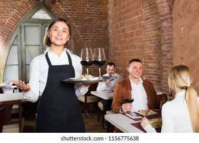 positive woman waiter demonstrating country restaurant to visitors