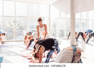 Positive woman yoga instructor rejoices and corrects the movement of their students during group classes in the gym. Yoga concept of meditation and pilates