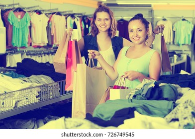 Positive women carrying bags with purchases and smiling in boutique