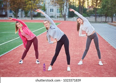 Positive women doing sport exercises..The group of three beautiful young women doing sport in sunny day in the park.