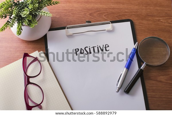 Positive word on paper with glass ballpen and green plant