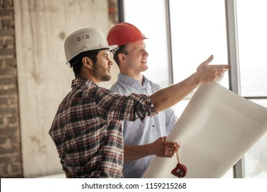 positive worker is showing the the progress of construction to a leader