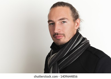 Positive young adult Asian man in black coat and woolen scarf stands over white wall background. Close up studio portrait