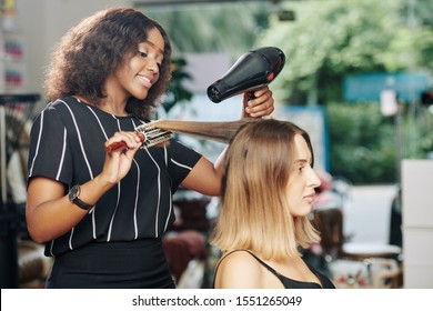 Positive young Black hairdresser enjoying working in beauty salon and blowdrying hair of client