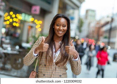 positive young business woman showing a thumbs up symbol