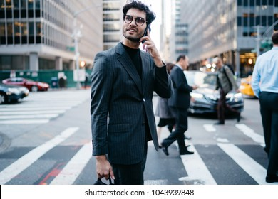 Positive young businessman talking on smartphone while looking away and crossing road in downtown of Manhattan.Successful banker in formal apparel communicating on cellular strolling in metropolis