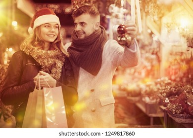 Positive young couple in Christmas hat buying decoration at Christmas fair outdoor