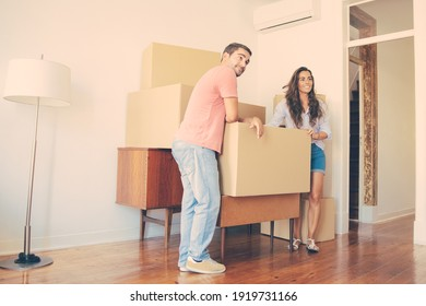 Positive young couple looking over their new apartment, while standing and leaning on cardboard boxes and furniture indoors. Full length. New home or property buying concept