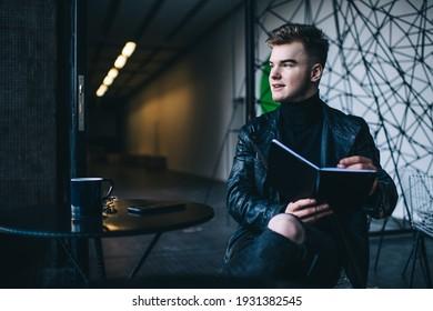 Positive junge kreative Künstlerin in trendiger Lederjacke sitzend am Tisch im Café und lächelnd beim Malen im Skizzenbuch