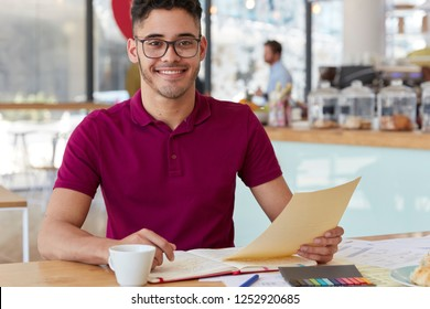 Positive young entrepreneur writes main theses for business deal, holds paper, enjoys paper work in coffee shop, drinks hot beverage from cup, wears casual clothes, has satisfied facial expression
