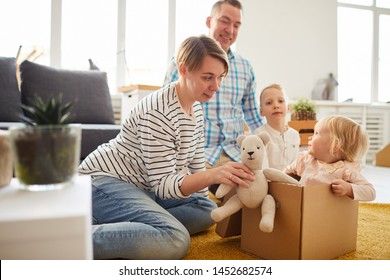 Positive young family playing with moving boxes into new house: content mother with curly hair giving toy bear to daughter sitting inside of cardboard box