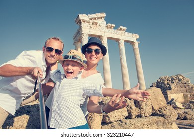 Positive young family take a selfie photo near antique colonnade