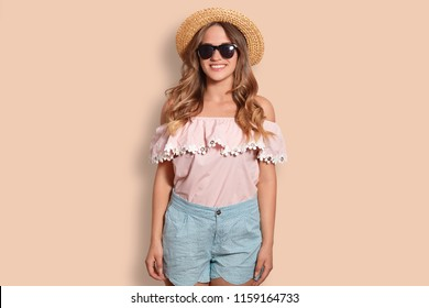 Positive young female in fashionable clothes, going on beach, has friendly positive smile, poses alone against studio background. Attractive tourist recreats in exotic country. People and vacation