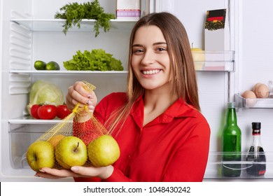 Positive young female with glad expression comes from grocer`s shop with new purchase, shows fresh apples, going to put them in fridge, stands at kitchen. Woman advertizes fresh fruit for you