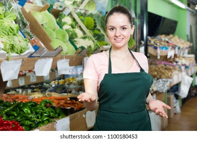 Positive young female grocery worker welcoming to a vegetable store