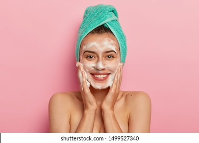 Positive young female has toothy smile, has perfect teeth, pats skin with liquid sanitary soap, washes with foaming gel, wakes up in morning for having beauty routine, isolated on pink background