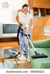 positive young female make cleaning at house using hoover