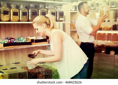 Positive young female package dried berries sold by weight in organic shop
