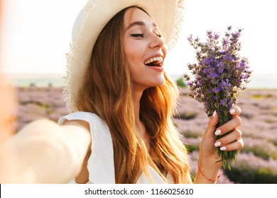 Positive young girl in straw hat holding lavender bouquet at the field, taking a selfie