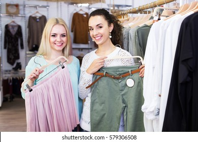 Positive young girls choosing new clothes in shopping center. Focus on brunette