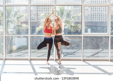 Positive young girls doing vrikshasana standing in the gym against the background of a large window. Concept of family training yoga and pilates