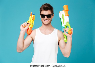 Positive young handsome brunette man in sunglasses looking camera and holding two water guns isolated over blue