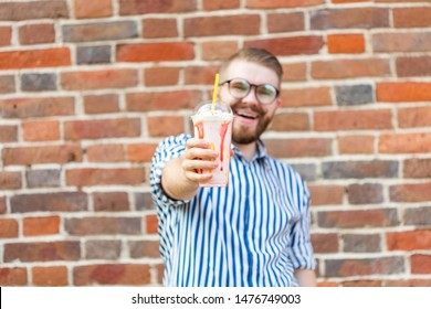 Positive young hipster guy in glasses and with a beard is holding a cocktail with a pipe posing against a brick wall. The concept of holidays and summer vacation.