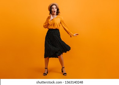 Positive young lady dancing on yellow background. Magnificent girl in straw hat and black skirt expressing amazement.