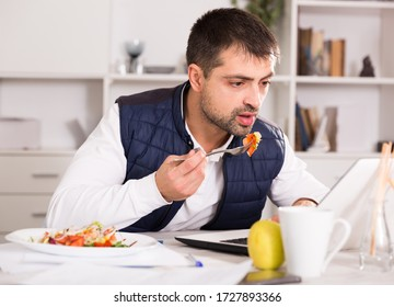 Positive young male holding  fork, eating vegetable salad at table with laptop