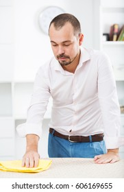 Positive young man cleaning his office desk by cleanser