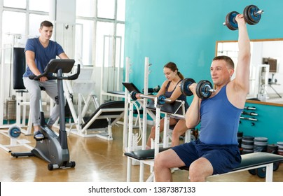 Positive young man doing exercises with sports dumbbells at gym