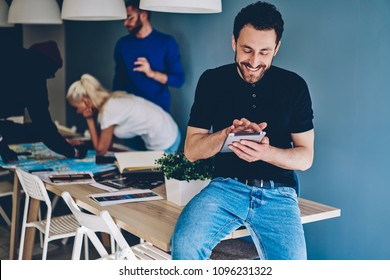 Positive young man dressed in smart casual wear laughing and chatting online on modern touch pad using 4G internet connection while team of colleagues collaborating on background in modern office