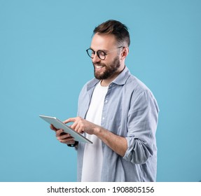 Positive young man in glasses using digital tablet for online work or studies on blue studio background. Happy teacher giving webinar. Blogger writing new post for social media