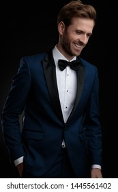 Positive young man laughing while holding his hand in his pocket and looking down, wearing a blue tuxedo while standing on black studio background
