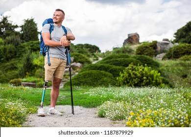 Positive young man with prosthesis standing outdoors while enjoying tourism