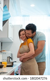 Positive young man standing in the kitchen behind the back of his beautiful smiling girlfriend and embracing her