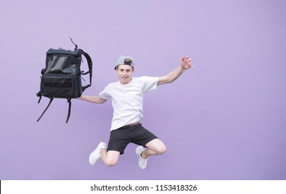 Positive young man in a white T-shirt jumping with a backpack against the background of a purple wall. Man jumping with a backpack on a purple background looks at the camera.
