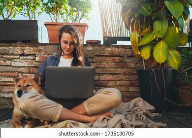 Muchacha joven y positiva de milenios con pelo largo sentada al aire libre en la terraza de la casa con el mejor perro amigo trabajando a distancia usando laptop, hermosa estudiante con reunión en video en línea vía computadora