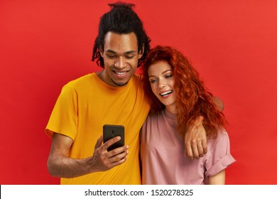 Positive young mixed race couple embrace each other, look joyfully at mobile phone, glad to view common photos, satisfied with good wireless connection, against red background. Relationship concept.