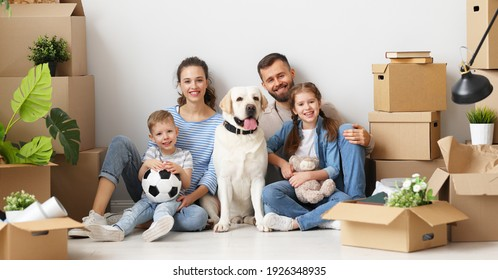 Positive young parents with little children and purebred dog smiling and looking at camera while sitting together on floor among carton boxes during relocation to new home