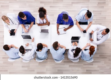 Positive Young Specialists With Stethoscope Having Discussion Of Research Work In Conference Room