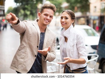 Positive young traveller asking woman direction at the street