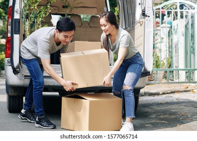 Positive young Vietnamese couple taking heavy cardboard boxes out of truck