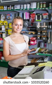 positive young woman cashier standing at pay desk in housewares store