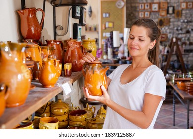 Positive young woman choosing handmade earthenware in pottery shop