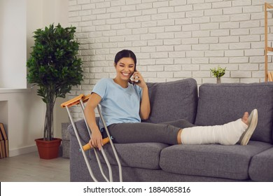 Positive young woman with crutches and broken leg in plaster cast sitting on sofa at home, talking to friend or relative on phone, telling about stupid funny accident which resulted in bone fracture