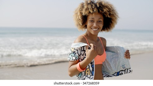 Positive young woman flirting on camera on the beach in