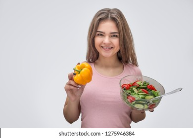 Positive young woman hold bowl with salad and yellow pepper in hands. She look on camer and smile. Isolated on grey background.