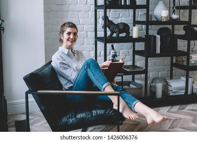 Positive young woman holding textbook in hands and looking away while sitting on chair at home, cheerful smiling hipster girl thinking on interesting literature plot from literature bestseller